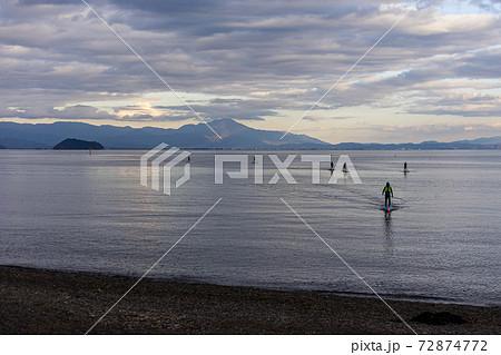 夕焼けの中で琵琶湖でSUPを楽しむ人達 72874772