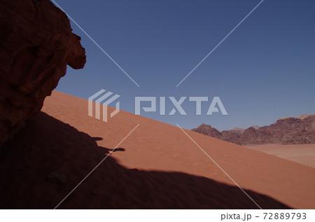【ヨルダン】アカバ、大砂漠ワディラムの赤茶色の砂丘と岩影 72889793