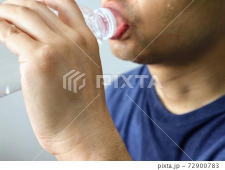 運動後に水分補給をする人物のクローズアップ 72900783