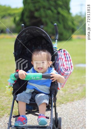 ベビーカーに乗っている笑顔の1歳の子供 72913818