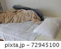 洋服が散らかった汚い部屋のベットと布団と枕 72945100