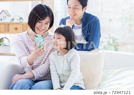 ファミリーのポートレート スマホを見る親子 72947121