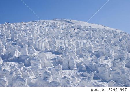 雪山の斜面を支配する樹氷と青空 72964947
