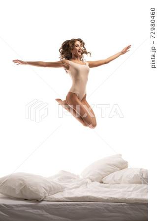 Happy slim model in bodysuit jumping over bed 72980460