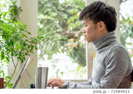 緑あふれるなオフィスで集中して仕事をする男性 72984633