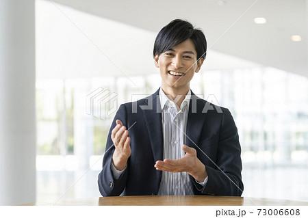 カメラ目線で話す若いビジネスマン 73006608