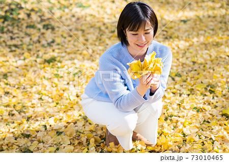 イチョウの葉を愛でる若い女性 73010465