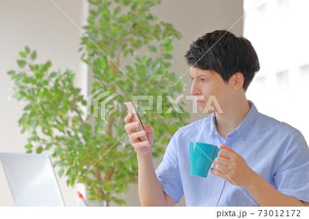 コーヒーカップを持ちスマホを見て困惑の表情のビジネスマン 73012172