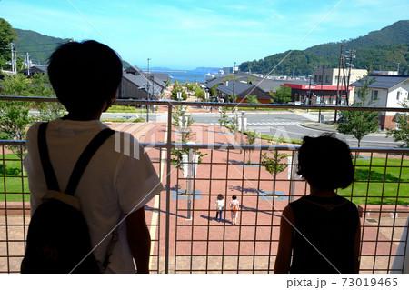 女川駅舎から街並みを見下ろす兄弟 73019465