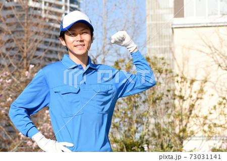 ガッツポーズを取る作業服姿の男性 73031141