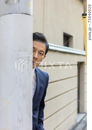 隠れて尾行する捜査官 73040029