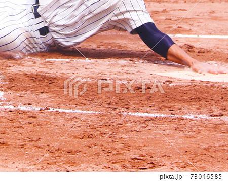 高校野球パーツ・きわどいタイミングでうまいスライディングでホームに滑り込み得点する選手 73046585