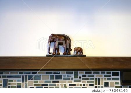 暖炉の上に置かれた象の親子の置物 73048146