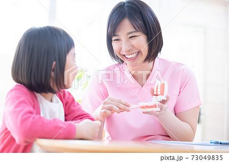 歯医者 歯磨き指導を受ける女の子と医師 73049835