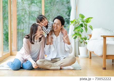 リビングに座ってパパに肩車をされてふざける女の子とパパとママの3人家族のポートレート 73052222
