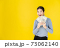 Black friday sales Ad Banner Portrait of Asian happy women holding money in a happy gesture looking at camera isolated on yellow background with copy sapce,shopping lifestyle financial concept. 73062140
