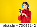 Asian women in the happy mood hold the phone and put the wireless headphone into the red dress. Choosing music from Mobile or studying E-leanning from mobile over yellow background with copy space. 73062142