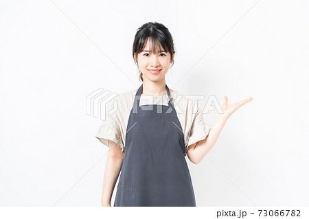 案内のジェスチャーをするエプロンを着た若い女性 73066782