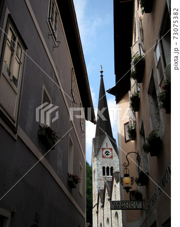 旅人を迎えるホテルやレストランが立つ狭い石畳の通りから仰ぎ見る教会の尖塔 73075382