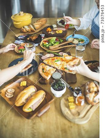 ホームパーティーで料理を食べる女性 73076453