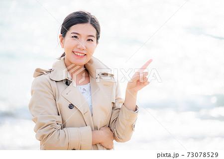 笑顔で指さしする女性 白く光る海の背景 73078529