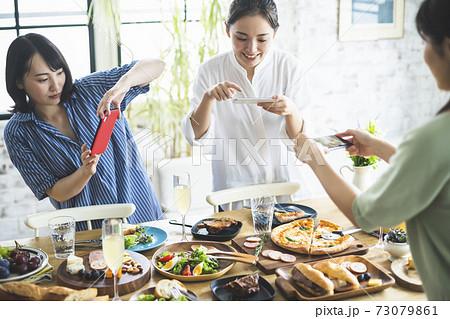 料理の写真を撮る女性 73079861
