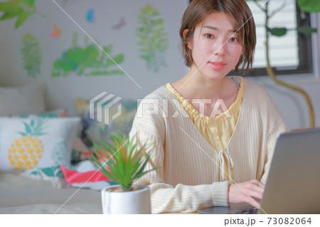 テレワーク_PCから目を上げ微笑む女性 73082064
