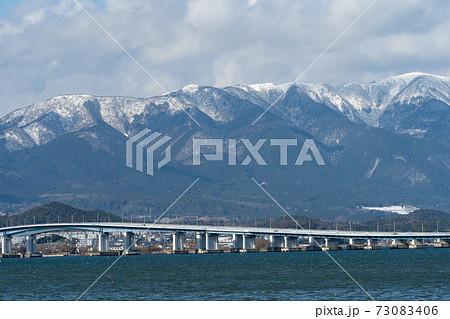 雪雲に覆われつつある比良山系と琵琶湖大橋の風景 73083406