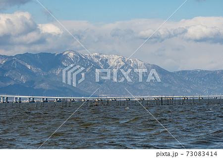雪雲に覆われつつある比良山系と琵琶湖大橋の風景 73083414