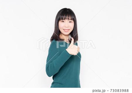 白背景の前に立って、いいねのジェスチャーをする女性 73083988