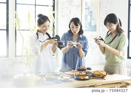 料理の写真を撮る女性 73084327
