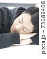 居眠りをする若い男性 73089408