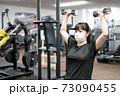マスクしてフィットネスジムで筋トレをする女性 73090455