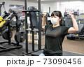 マスクしてフィットネスジムで筋トレをする女性 73090456