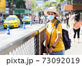 Asian women tourists visit Bangkok. A female traveller wearing a mask is looking at the camera while visiting a backpacker during the outbreak in new normal lifestyle with blur background, copy space. 73092019