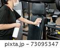 トレーニングジムのマシンを消毒する女性 73095347