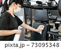 トレーニングジムのマシンを消毒する女性 73095348