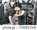 トレーニングジムのマシンを消毒する女性 73095349