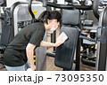トレーニングジムのマシンを消毒する女性 73095350