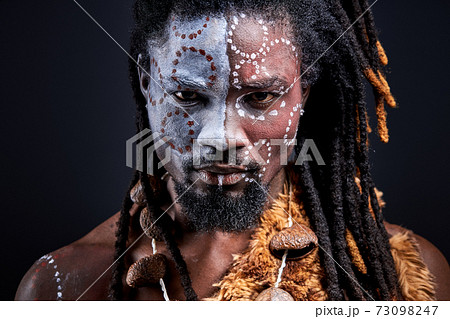 afro american shaman with national ethnic make-up on body 73098247