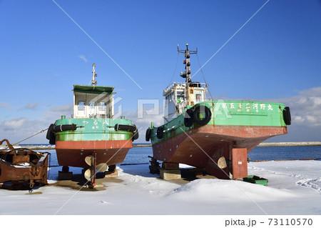 冬の北海道森町森漁港で陸揚げされているタグボートの雪景色を撮影 73110570