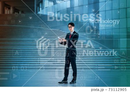 オフィスでスマホを操作するビジネスマンのネットワークイメージ 73112905