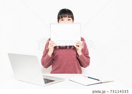 ノートパソコンを使いながら、小さいスケッチブックを持つ女性 73114335