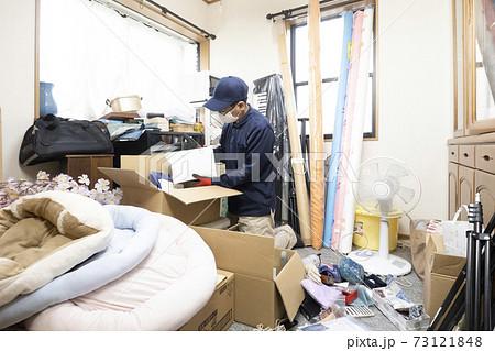 散らかった部屋と片付ける作業員 73121848