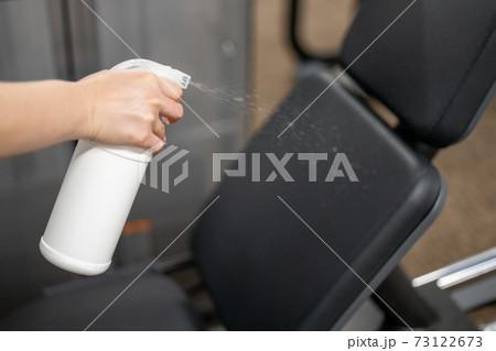 トレーニングジムのマシンに消毒液をスプレーする腕 73122673