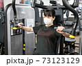 マスクしながらフィットネスジムで胸を鍛える女性 73123129