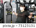 マスクしながらフィットネスジムで胸を鍛える女性 73123131