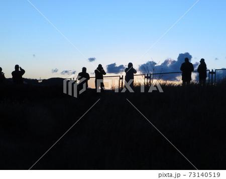 日出の方向に受かってカメラを構える人々 73140519