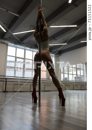 Unrecognizable sexy woman performing alluring pole dance 73151522