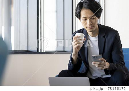 スマートフォンの画面を見る若い男性 若いビジネスマンイメージ 73156172